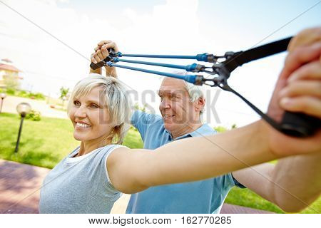 Cheerful senior couple working out with resistance band