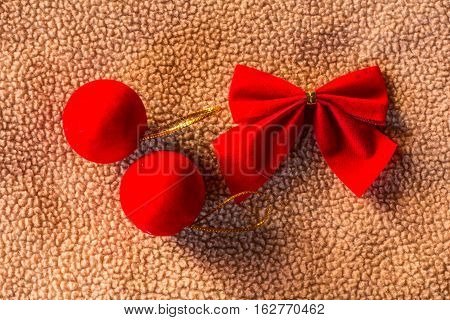 Red ball with bow on fabric christmas still life
