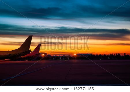 the silhouette of airplane are parking at air port in twilight sky background
