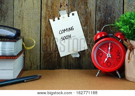 Coming soon text written on sticky note. Book, pen, spectacle and red clock on brown desk. Education and business concept.