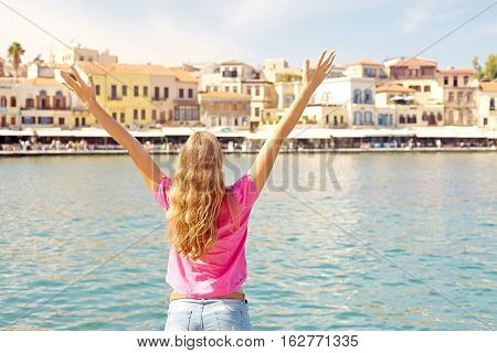 Rear view of woman standing by the sea with outstretched arms