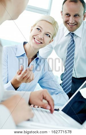 Young smiling office worker asking her colleague about something