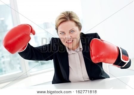Portrait of aggressive businesswoman in boxing gloves