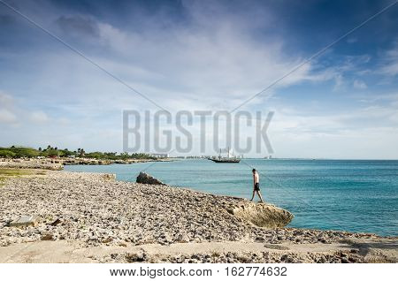 Man Walking With A Sailboat Anchored As A Background