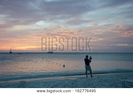 Photographer At The Sunset With Anchored Sail Boats