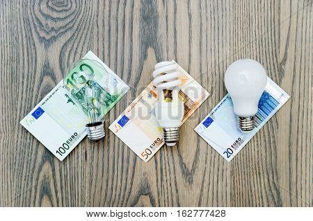 LED bulb saves money. The photo shows three lights: LED fluorescent and incandescent. Money bills related costs for energy consumption.