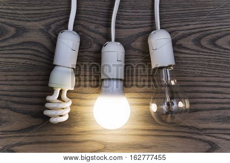 LED bulb saves money. The photo shows three lights: LED fluorescent and incandescent.