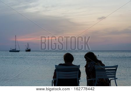 Tourists At The Sunset With Anchored Sail Boats
