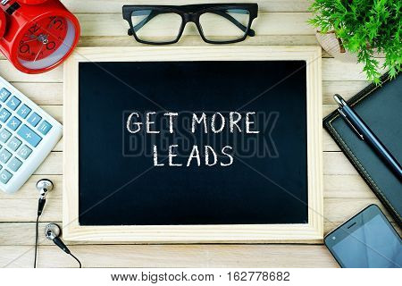 Top view of earphone, calculator, alarm clock, spectacle, notebook, pen, smartphone and chalkboard written with GET MORE LEADS.