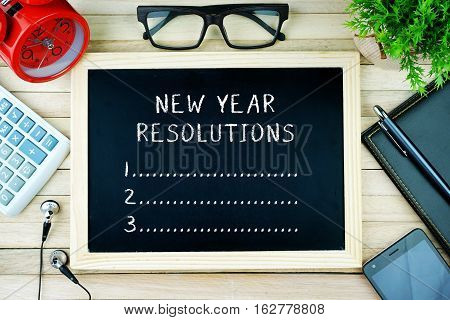 Top view of earphone, calculator, alarm clock, spectacle, notebook, pen, smartphone and chalkboard written with NEW YEAR RESOLUTIONS.
