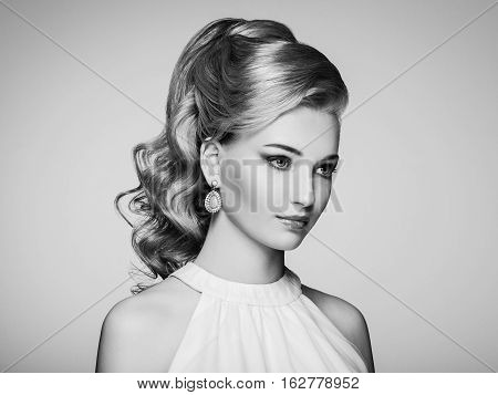 Fashion portrait of young beautiful woman with jewelry and elegant hairstyle. Blonde girl with long wavy hair. Perfect make-up. Beauty style woman with diamond accessories. Black and White