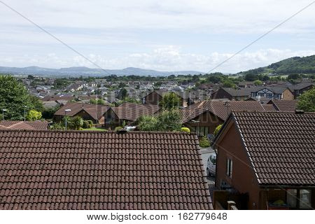 Row house roofs, condo rooftop panorama and bright summer cloudscape with Mountains in background UK