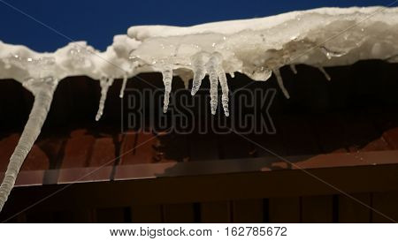 Icicles roof hanging off roof in the dripping winter spring warming nature