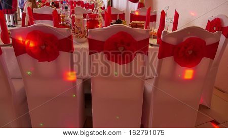 chairs in a restaurant decorated ribbons flashes lumiere holiday