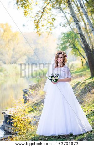 Young bride stands on the shore of the lake. Bright sunny day. Young beautiful bride in white dress velekolepnom stands on the shore of the lake.
