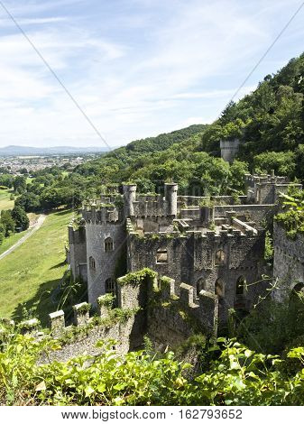 Gwrych Castle Portrait In Summer, Wales Uk Surrounded By Trees And Foliage On Hill Side.