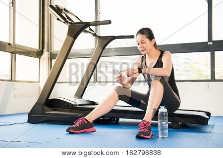 Asian Woman Rest Sitting Treadmill Use Smartphone And Smartwatch
