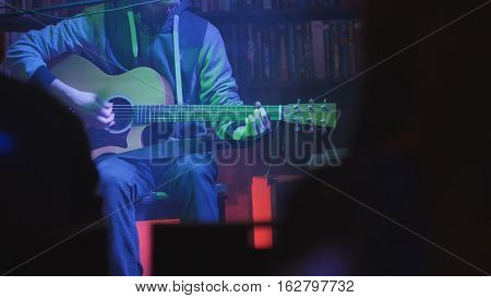 Guitarist plays acoustic guitar in night club, close up, telephoto