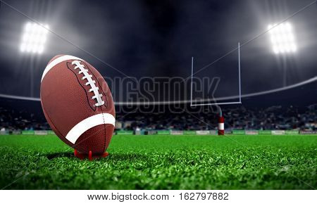 American football in stadium at night with spotlight