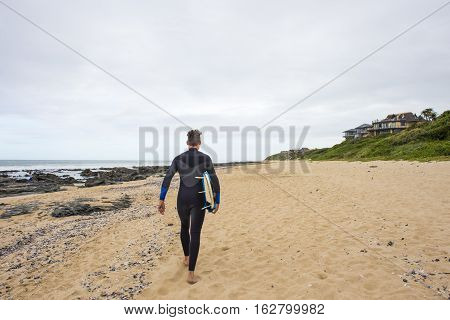 A surfer in a wetsuit walks along the beach with his surfboard under his arm.