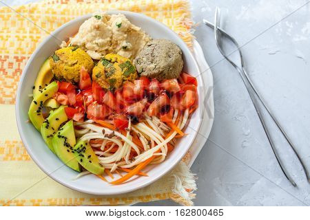 Zucchini carrots spaghetti with vegan balls avocado and hummus. View top on gray concrete background. Vegan Food Concept.