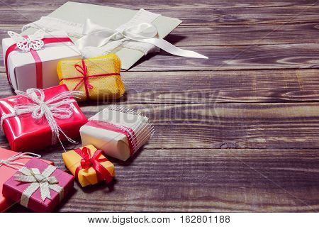gifts in different colorful packages on a wooden background
