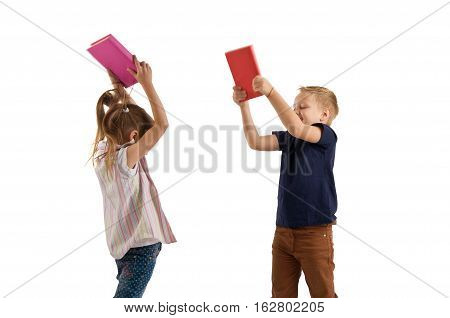 Two schoolchildren quarrel and fight with books