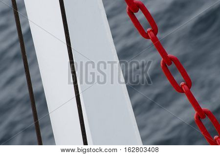 Red chain of anchor hanging on water against the sea