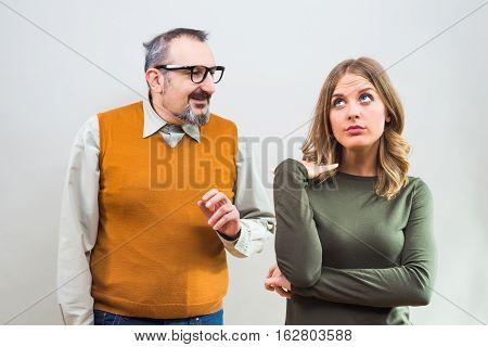 Nerdy man is trying to get beautiful woman's attention but she is not interested and angry ignore him.