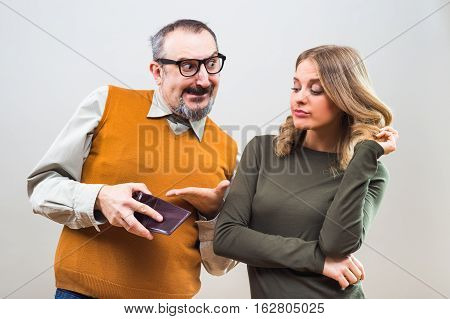 Nerdy man is trying to get attention from a beautiful woman by showing her his wallet full of money but she is still not interested.