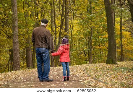 Grandfather and granddaughter spend the weekend in the park. Autumn