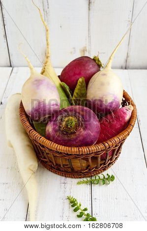 Several kinds of radish (daikon Chinese red green) in a basket on a white wooden background. Useful vitamins ingredient for salads.