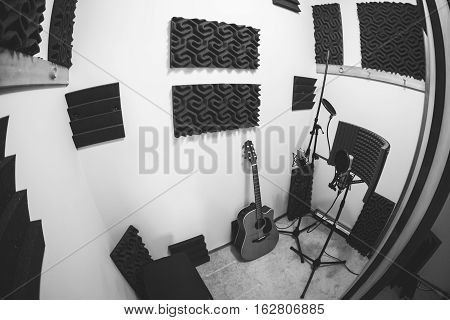 Recording booth in closet of recording studio. Acoustic foam, guitar, microphones, and related equipment.