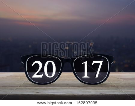 2017 text with eye glasses on wooden table over blur aerial view of cityscape on warm light sundown Business success concept