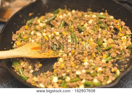 Cooking a casserole with ground meat, green beans, corn, Home made casserole in an iron skillet with wooden spatula.