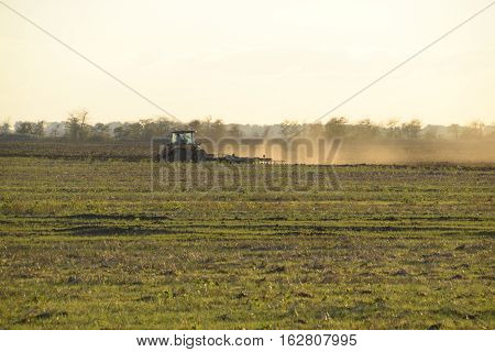 Tractor At Sunset Plow Plow A Field. Tilling The Soil In The Fall After Harvest. The End Of The Seas