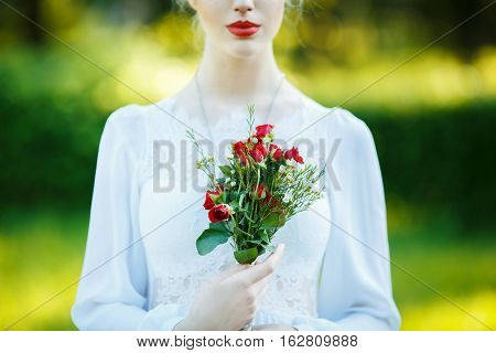 Fine art outdoor portrait of beautiful young blonde woman in a white dress. Girl holding a beautiful flower bouquet