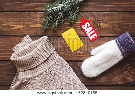 Christmas clothing sale on wooden background top view.