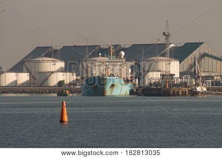 Huge tanker ship moored to a wharf.