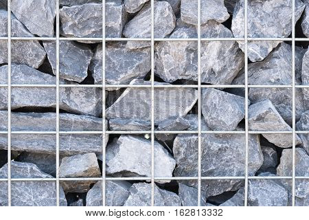 Steel mesh of gabion wall.Grey stones in gabion.