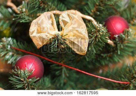 Beautiful golden bow and red, green Christmas balls on artificial Christmas tree close up detail