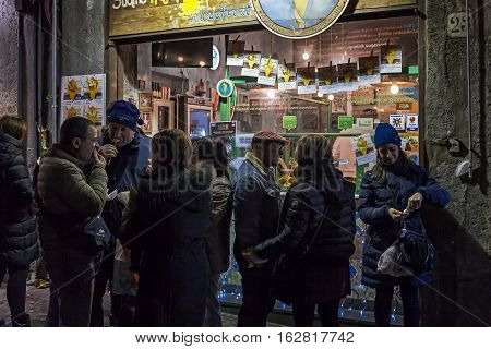Naples Italy - December 9 2016: People in the street still eat cooked food at the moment in front of a typical Neapolitan fry.