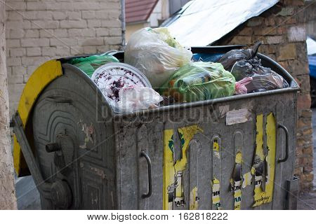 Outdoor trash bin with food waste. Not sorted garbage, yard, stench, filth, carelessness. Steel container
