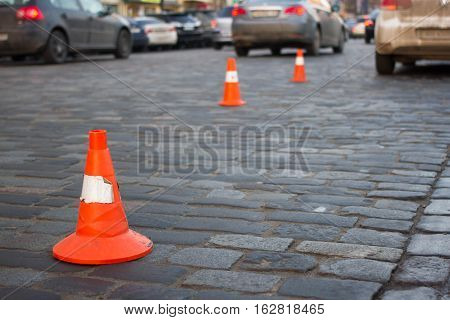 Traffic cone stay on paving stone on street. Limit for car parking