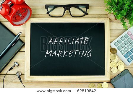 Top view of earphone, calculator, alarm clock, spectacle, notebook, pen, smartphone and chalkboard written with AFFILIATE MARKETING.