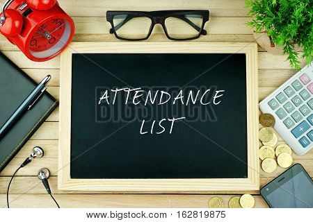 Top view of earphone, calculator, alarm clock, spectacle, notebook, pen, smartphone and chalkboard written with ATTENDANCE LIST.