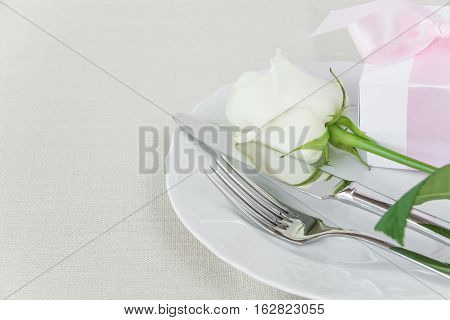 Beautiful decorated table with white plates gift box with a pink ribbon cutlery and white rose flower on tablecloths with space for text