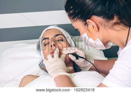 Young pretty woman getting rf lifting treatment on clinical center. Medicine, healthcare and beauty concept.