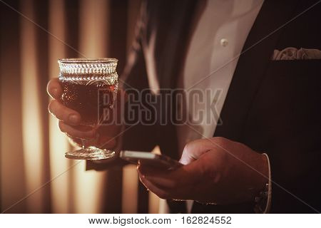 Young ginger bearded man holding a vintage glass with red wine against the light. black on background. guy looking in the phone.