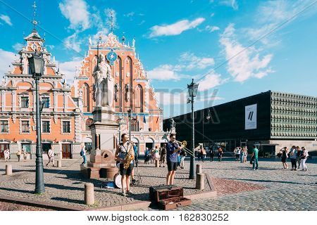 Riga, Latvia - July 1, 2016: Street Music Trio Band Of Three Young Musicians Guys Playing The Instruments For Donation On The Town Hall Square, Famous Touristic Showplace Of Old Town In Sunny Summer.